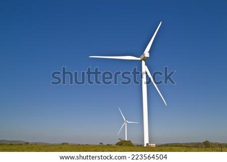 Two large wind turbines creating renewable energy - stock photo