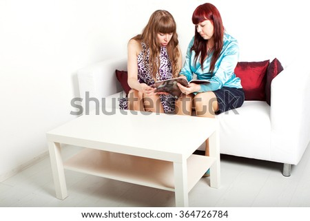 two lass reads a magazine - stock photo