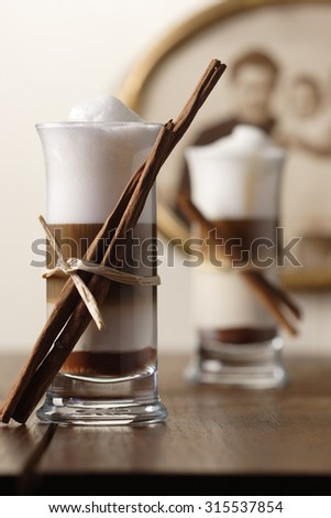 Two Latte Macchiato Nougat with cinnamon flavour and cinnamon sticks - stock photo