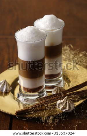 Two Latte Macchiato Nougat with cinnamon flavour and cinnamon sticks on a golden tray - stock photo
