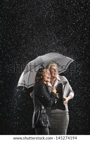 Two laughing businesswomen standing under an umbrella together in rain - stock photo