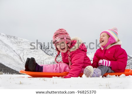 Two laughing kids sledding with a mountain scene in background - stock photo