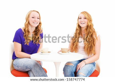 two laughing redhead women sitting at a coffee table on white background - stock photo