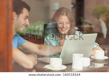 Two laughing students looking at laptop in college canteen - stock photo