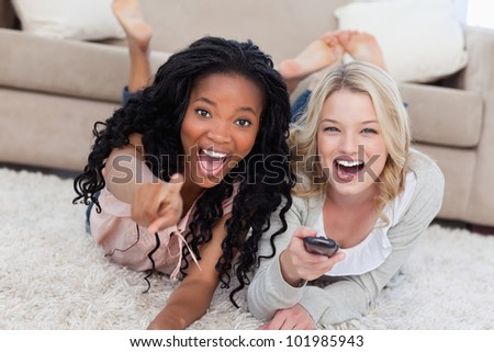 Two laughing women are lying on the ground and looking at the camera with a TV remote control