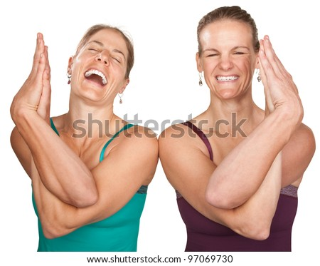 Two laughing women performing entwined namaskar over white background - stock photo