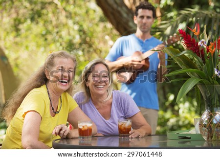 Two laughing women with ukelele player behind them - stock photo