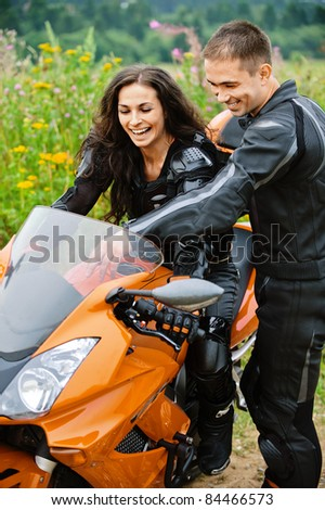 Two laughing young people: pretty brunette lady sitting on motorbike and handsome dark-haired man standing near.