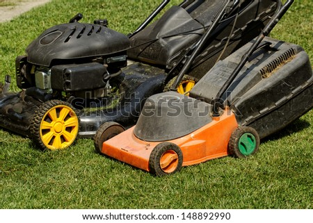 two lawnmower in the garden lawn the grass (fuel and electricity) - stock photo