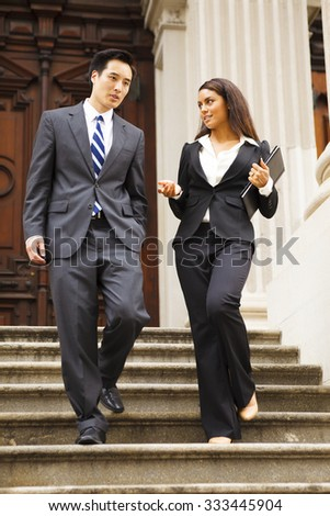 Two lawyers walk down the staircase of a courthouse. They are smiling and chatting. Could also be lawyer and client or lawyer and assistant.