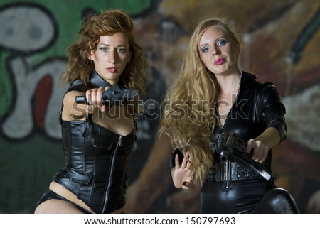 Two leather clad gun women aiming in the camera