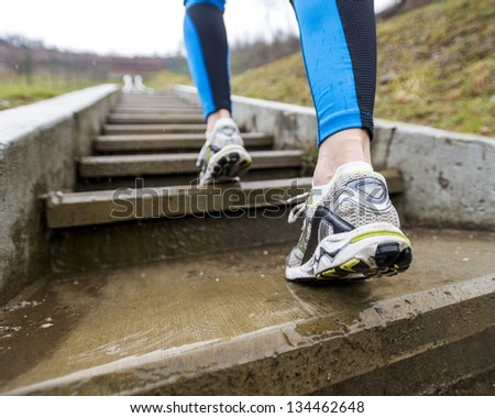 Two legs up the stairs we go to the mountain running - stock photo