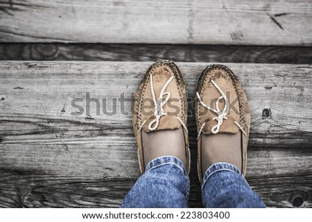 two legs wearing orange chamois moccasins with ties and denim jeans on wooden background near the sea - stock photo