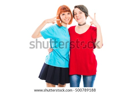 Two lesbian girls hugging and shows a peace sign on their fingers. On white, isolated background.
