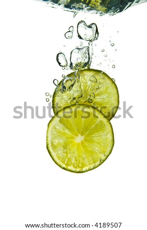 Two lime slices into water on white - stock photo