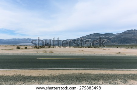 Two line road in Mojave desert with cloudy sky and striped mountains on background. Death Valley National Park, California  - stock photo
