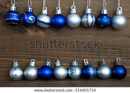Two Lines of Blue and Silver Christmas Balls, some with Decoration, on Wood with Copy Space for Your Text, Christmas or Winter Background - stock photo