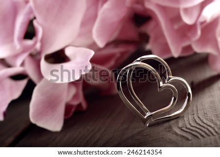Two linked silver hearts on a plank on a floral background in vintage style - stock photo