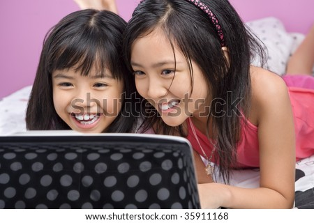 Two little Asian girls playing with laptop in the bedroom