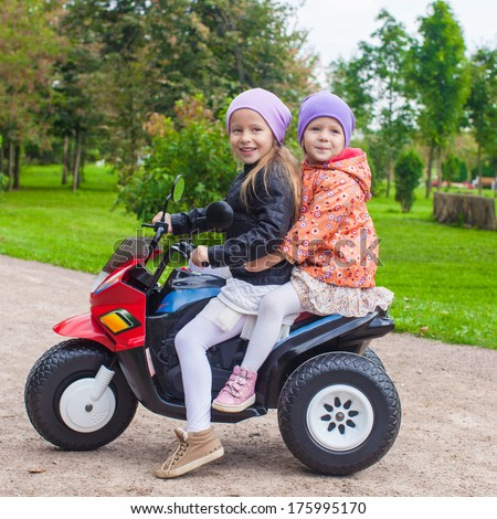Two Little beautiful sisters sitting on toy motorcycle in green park - stock photo