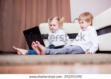 two little blond baby boy and a fair-skinned girl (brother and sister) sitting on the floor with a laptop, watch cartoons and play computer games - stock photo