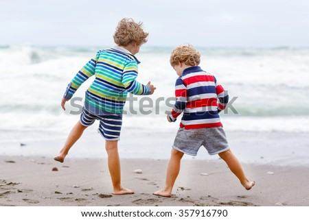 Two little blond kid boys having fun on lonely ocean beach. Twins children playing and running on stormy windy bad weather day. - stock photo