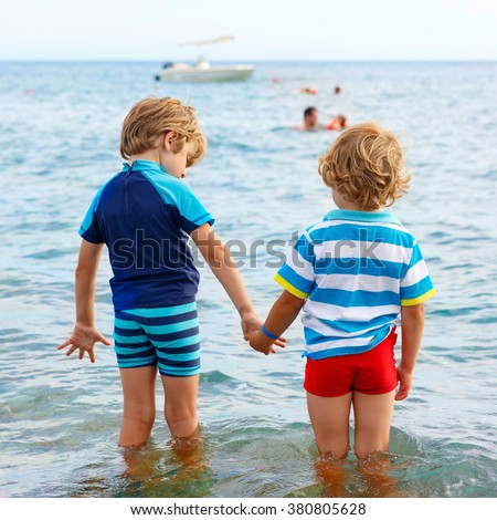 Two little blond kids boys having fun by taking bath in ocean or sea. Funny siblings, children holding hands. Vacations, summer, travel concept. Twins enjoying summer vacations on sea.  - stock photo