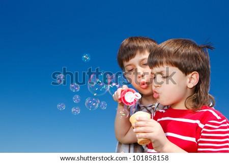 Two little boys blowing soap bubbles - stock photo