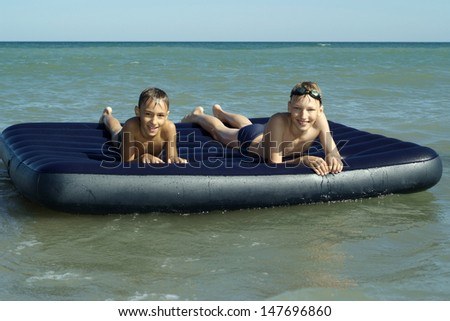 two little boys floating on air mattress - stock photo
