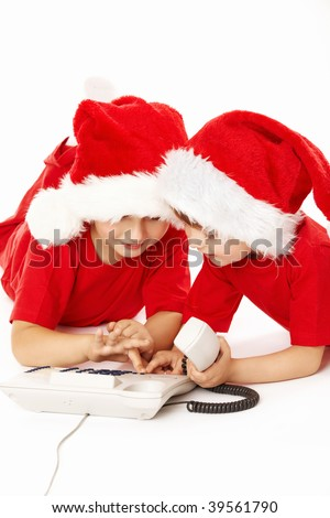 Two little boys in caps of santa dial a phone number, isolated - stock photo