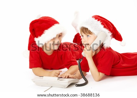 Two little boys in caps santa call by phone, isolated - stock photo