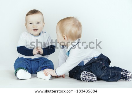 Two little boys in the studio, one sitting and laughing, the other touching his feet. - stock photo