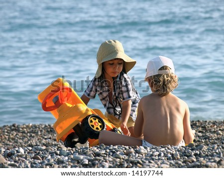 Two little boys playing on the beach - stock photo