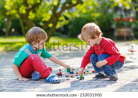 Two little boys playing together with car toys in summer garden
