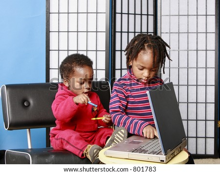 Two little boys playing with a computer