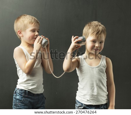 Two little boys playing with self-made phone - stock photo