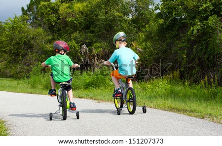 two little boys riding their bikes along a park trail