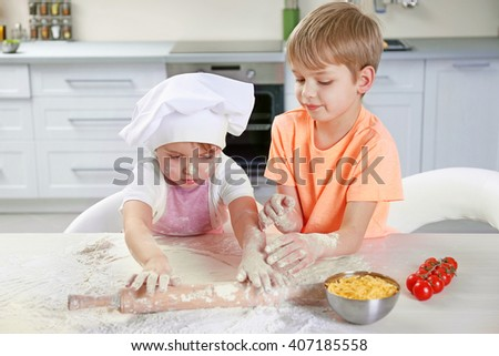 Two little boys rolling out a pizza dough, close up