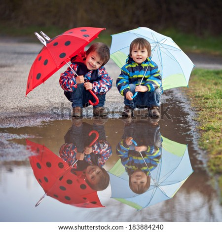 Two little boys, squat on a puddle, with little umbrellas - stock photo