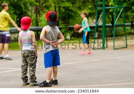 Two little boys standing side by side on the court with their backs to the camera watching a basketball game or training session - stock photo