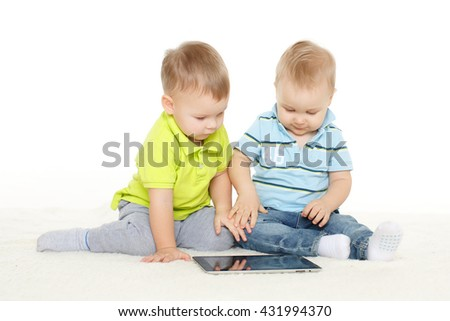 Two little boys with computer tablet  sit on a floor on a white background. - stock photo