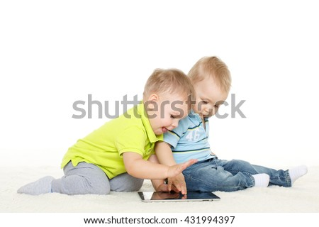 Two little boys with computer tablet  sit on a floor on a white background.