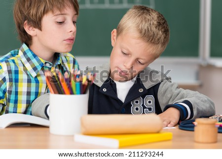 Two little boys working together in class as a team sitting at a desk working on a joint project