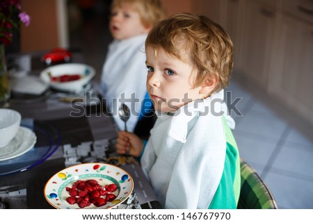 Two little brother boys having oat mash and berries for breakfast - stock photo