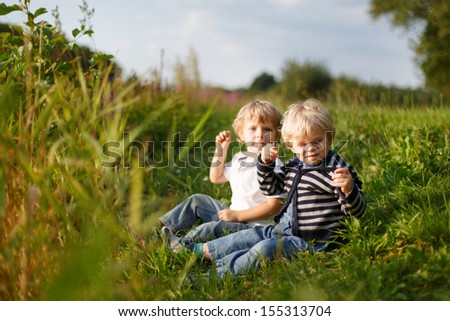 Two little brother boys playing near forest lake on summer evening. Selective focus on boy