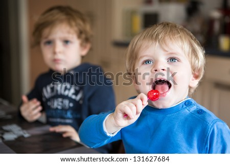 Two little brother boys watching tv and eating candy indoor - stock photo