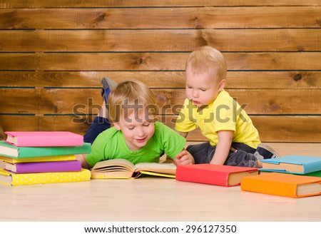 two little brothers in green and yellow shirts reading colored books on floor on brown wooden wall background - stock photo