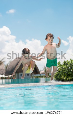 Two little brothers jumping into swimming pool - stock photo