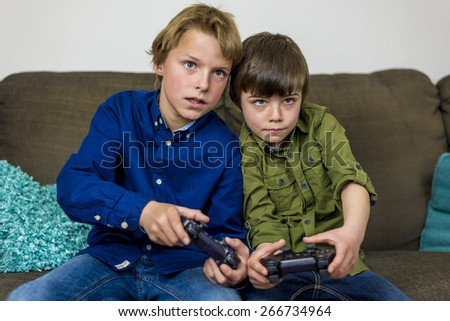 two little brothers on a couch,playing a computer game - stock photo