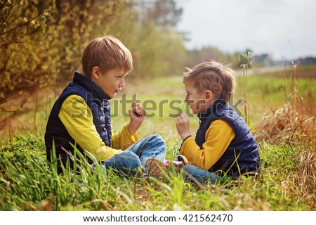 Two little brothers play in rock-paper-scissors sitting on grass in the summer park - stock photo
